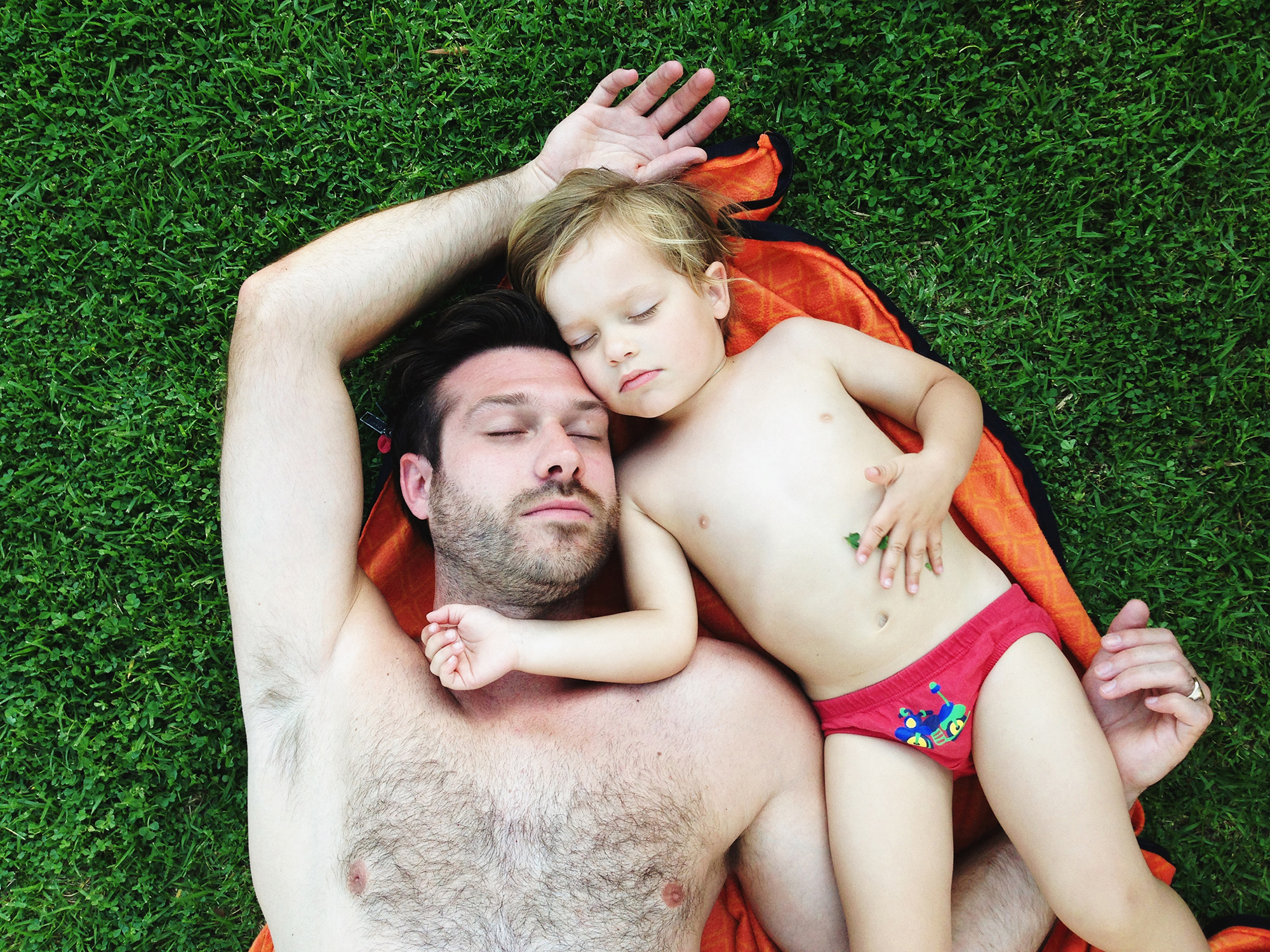Father and son taking a nap on the grass. Photo by STUDIO 1208